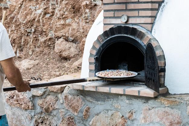 Mężczyzna wkładający pizzę do ręcznie malowanego na biało piecu na drewno zbudowany na zewnątrz z łopatą, tło