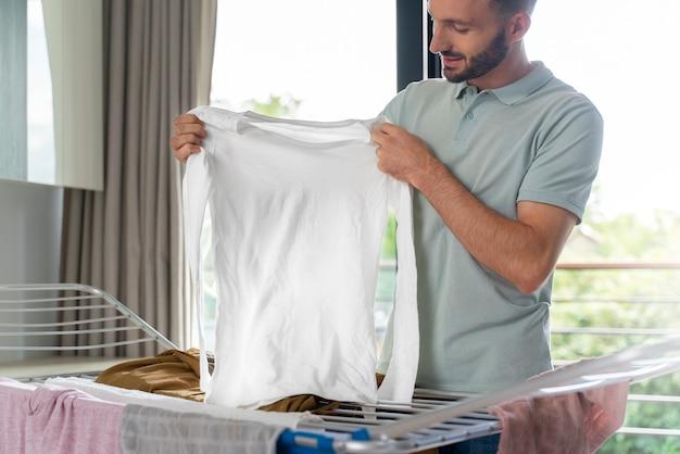 Mężczyzna wkładający ubrania do suszarki w pomieszczeniu