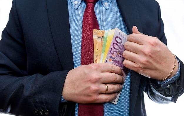 Mężczyzna wkładanie banknotów euro do kieszeni kurtki