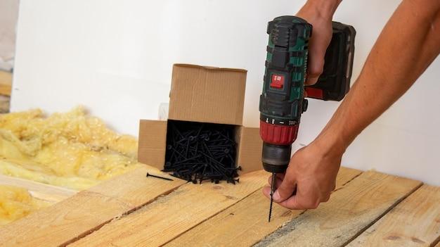 Mężczyzna wkręca śruby w deskę. naprawa podłogi w domu. selektywne skupienie. pochować