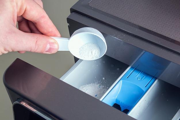 Mężczyzna wlewa mydło w proszku, wlewa odżywkę, środek zmiękczający skórę na tacę pralki.