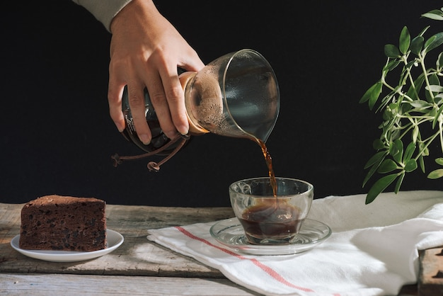 Mężczyzna wlewający kawę na zimno do szklanki na stole