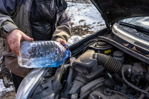 Mężczyzna wlewający płyn niezamarzający do specjalnego zbiornika płynu
