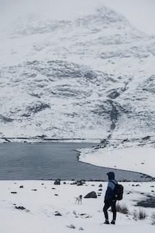 Mężczyzna woła swojego psa w zaśnieżonym parku