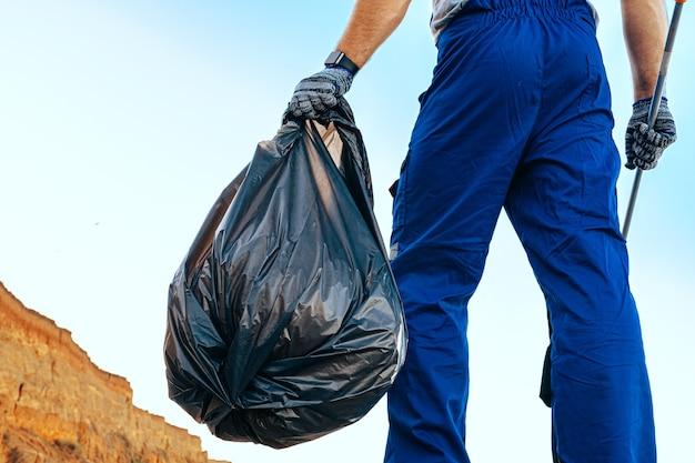Mężczyzna wolontariuszem w uniforn zbierającym śmieci na plaży z przedłużaczem zasięgu
