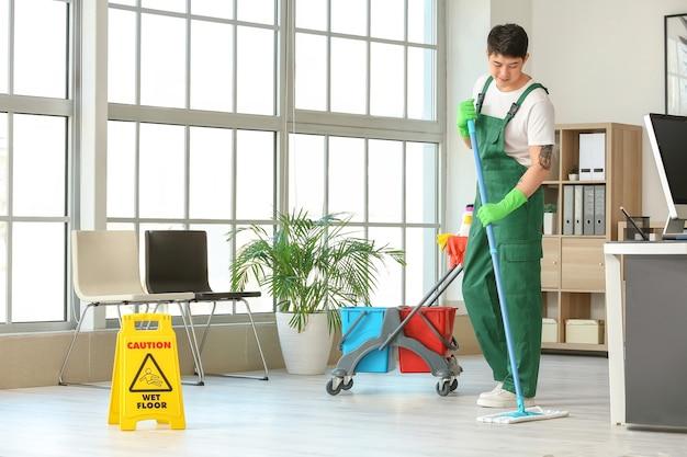 Mężczyzna woźny mopuje podłogę w biurze