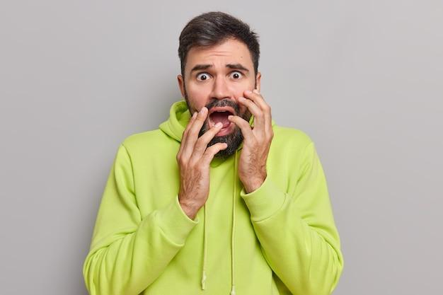 Mężczyzna wpatruje się intensywnie w kamerę trzyma usta szeroko otwarte czuje się zaniepokojony czymś ma poważne problemy obserwuje coś strasznego nosi zieloną bluzę pozuje na szarej ścianie