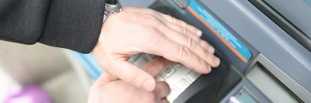 Mężczyzna wpisuje kod na klawiaturze bankomatu i zamyka go ręką