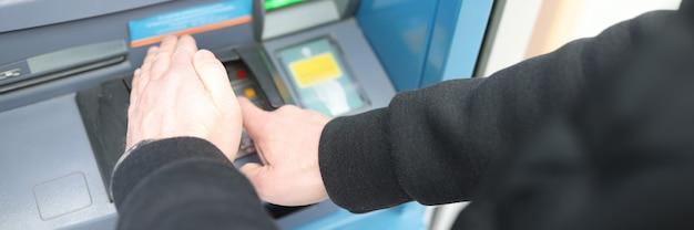 Mężczyzna wpisuje kod pin w bankomacie i zakrywa go dłonią z bliska