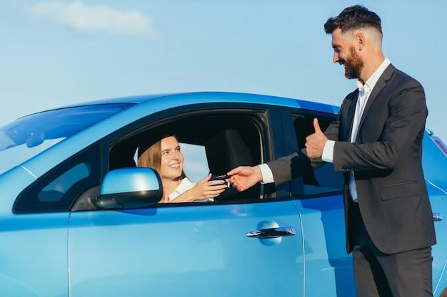 Mężczyzna wręcza kluczyki kobiecie siedzącej w samochodzie