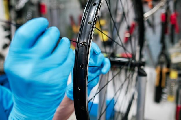 Mężczyzna wręcza naprawianie mówił mówił na roweru kole