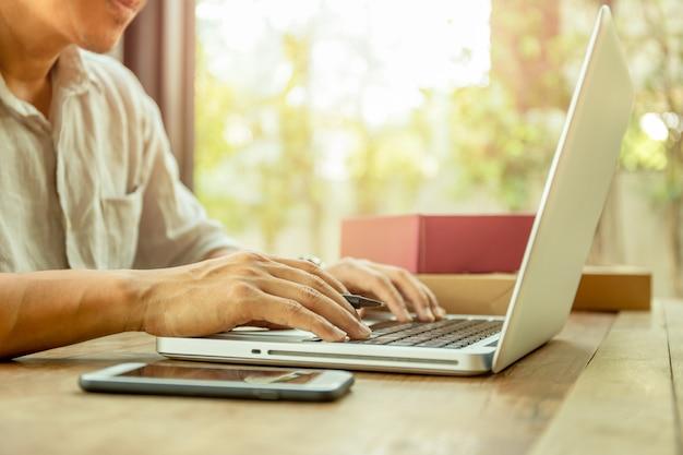 Mężczyzna wręcza pisać na maszynie na laptop klawiaturze z pakunkiem pakuje dostawę na stole.