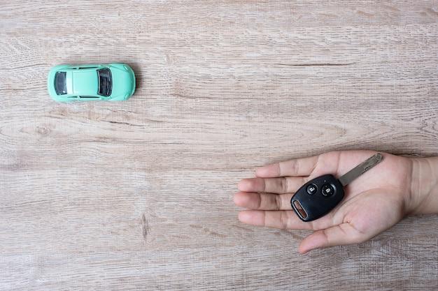 Mężczyzna wręcza trzymać klucz samochód. bankowość, ubezpieczenia, finanse, samochód za gotówkę