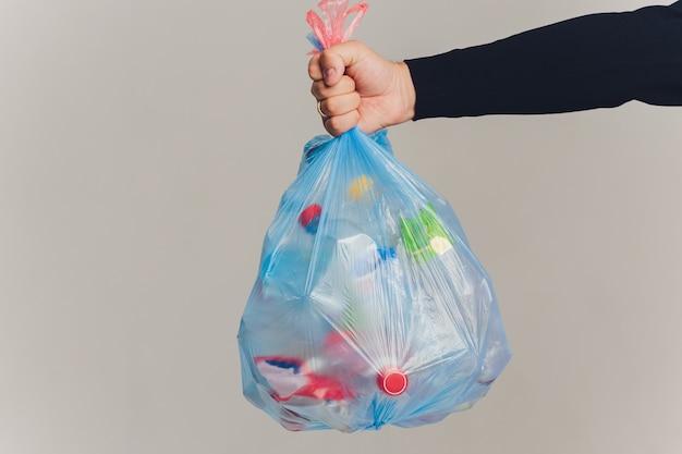 Mężczyzna wręcza trzymać torba na śmiecie odizolowywający na bielu
