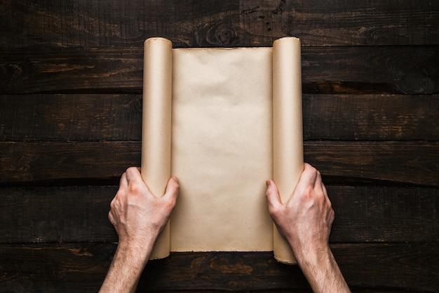 Mężczyzna wręcza trzymać zaakcentowaną papierową rolkę na starym barwood tle. kreatywna koncepcja wyprawy wanderlust. puste miejsce, miejsce na tekst, napis. makieta transparent poziomy.