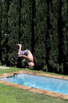 Mężczyzna wskakuje do salta w basenie. do góry nogami, wskocz do wody. odpoczynek, wakacje nad morzem. piękny widok