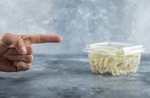 Mężczyzna wskazał palcem na słoik sera. wysokiej jakości zdjęcie