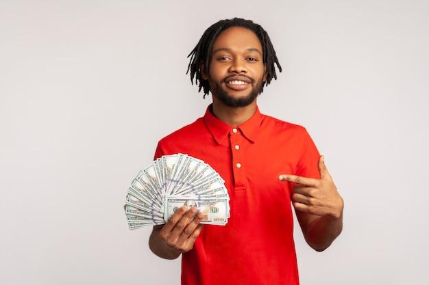 Mężczyzna, wskazując na banknoty dolarowe i patrząc ze szczęśliwym wyrażeniem, pożyczka bankowa, oszczędności finansowe.