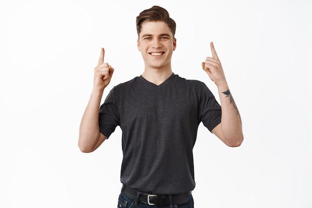 Mężczyzna, wskazując w górę i uśmiechając się, szczęśliwy wskazuje na nazwę marki i wygląda na zadowolonego, poleca przedmiot na białym