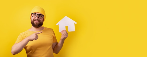 Mężczyzna wskazujący na dom na żółtym tle, obraz panoramiczny