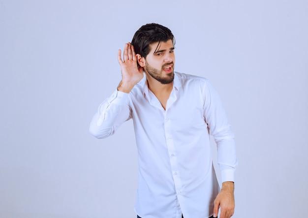 Mężczyzna wskazujący na ucho, ponieważ nic nie słyszy.