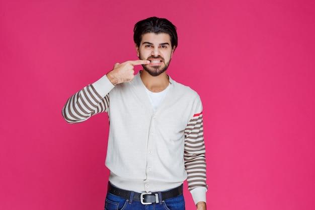 Mężczyzna wskazujący palcami zęby lub usta, co oznacza uśmiech lub zdrowie jamy ustnej.