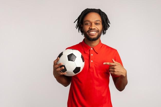 Mężczyzna wskazujący palcem na piłkę nożną na dłoni z uśmiechniętym pozytywnym wyrazem twarzy