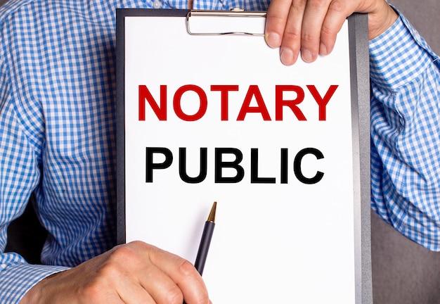 Mężczyzna wskazuje długopisem tekst notariusz publiczny na białej kartce