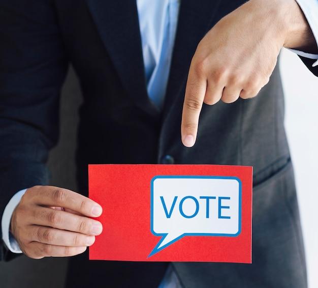 Mężczyzna wskazuje na jego kartę do głosowania