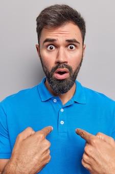 Mężczyzna wskazuje na siebie patrzy wyłupiastymi oczami zaskoczony, że został wybrany, ubrany w casualową niebieską koszulkę na szarym tle