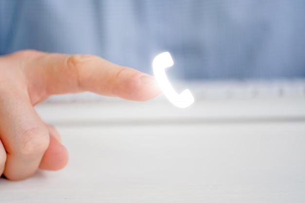Mężczyzna wskazuje palcem na ikonę telefonu. zadzwoń, aby wykonać połączenie.