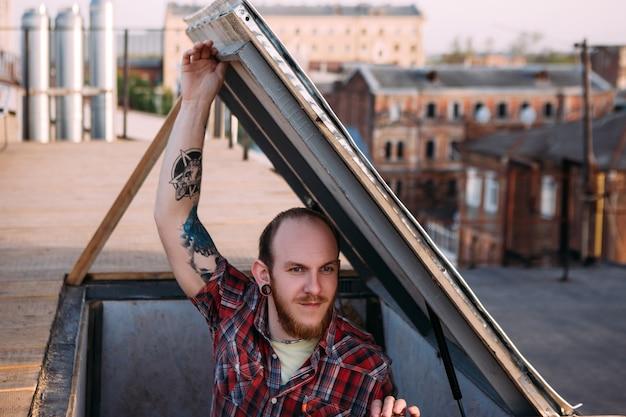 Mężczyzna wspinaczka na dachu. kreatywny czas wolny. romantyczna randka, młody stylowy hipster skupiony na pierwszym planie, niebezpieczna subkultura parkour, koncepcja miejska