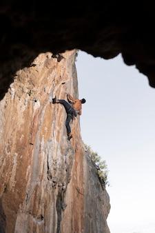 Mężczyzna wspinający się na górę ze sprzętem bezpieczeństwa