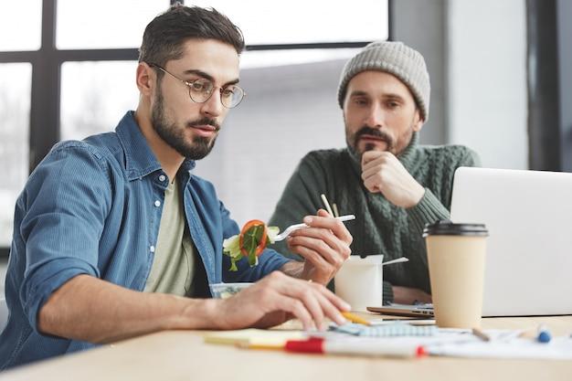 Mężczyzna współpracowników w biurze z lunchem