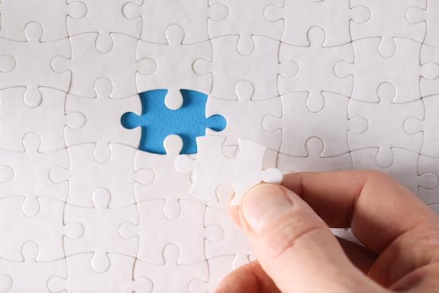 Mężczyzna wstawiający ostatni kawałek do białego puzzla zbliżenia
