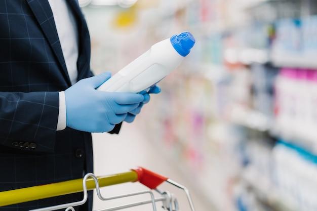 Mężczyzna wybiera detergent w sklepie z artykułami gospodarstwa domowego, trzyma butelkę z płynnym proszkiem, nosi rękawice medyczne w celu ochrony przed koronawirusem, czyta informacje o produkcie. robienie zakupów podczas kwarantanny