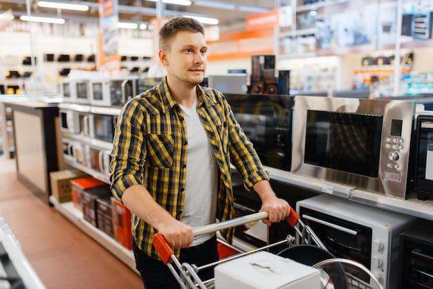 Mężczyzna wybiera kuchenkę mikrofalową w sklepie elektronicznym