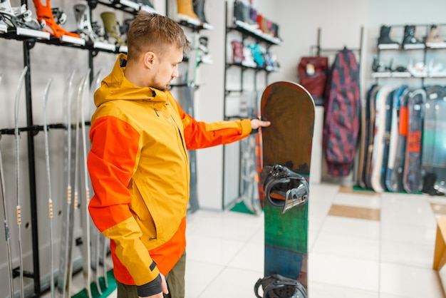 Mężczyzna wybiera snowboard, zakupy w sklepie sportowym