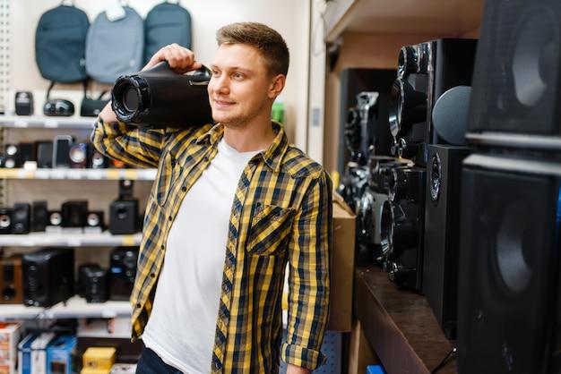 Mężczyzna wybiera system muzyczny w sklepie elektronicznym. mężczyzna kupuje domowe urządzenia elektryczne na rynku