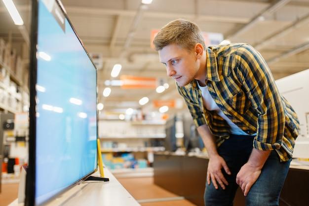 Mężczyzna wybiera telewizor plazmowy w sklepie elektronicznym