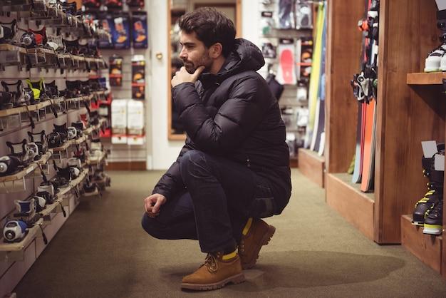 Mężczyzna wybiera w sklepie wiązania narciarskie