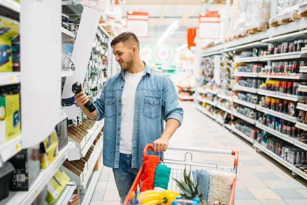 Mężczyzna wybiera wkrętarki elektryczne, dział elektronarzędzi w supermarkecie, rodzinne zakupy. klient z koszykiem w sklepie