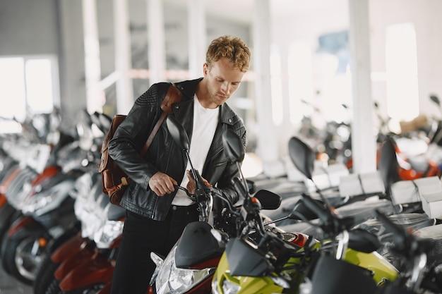 Mężczyzna wybrał motocykle w sklepie moto. facet w czarnej kurtce.
