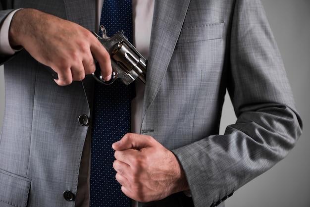Mężczyzna wyciąga broń z kieszeni