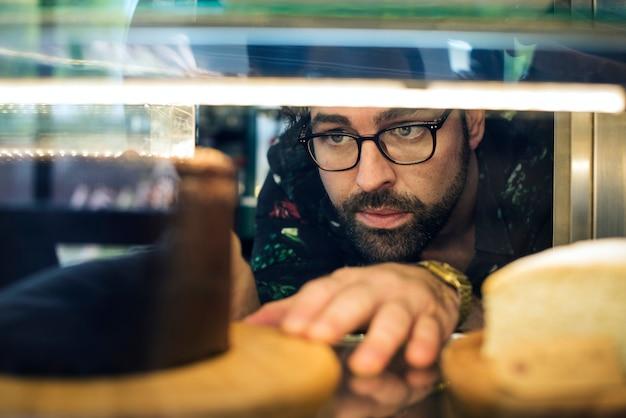Mężczyzna wyciąga ciasto z lodówki wystawowej