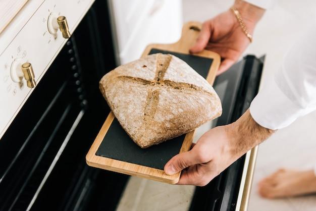 Mężczyzna wyciąga gorący chleb z piekarnika
