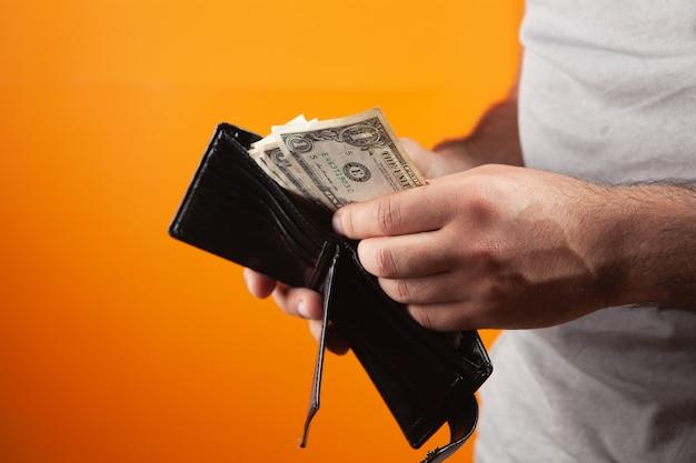 Mężczyzna wyciąga pieniądze z portfela na pomarańczowym tle
