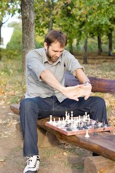 Mężczyzna wyciąga ręce przed sobą, siedząc okrakiem na drewnianej ławce i grając w szachy