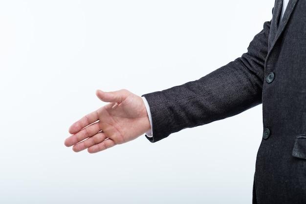 Mężczyzna wyciąga rękę do uścisku dłoni. spotkanie biznesowe lub rozmowa kwalifikacyjna.