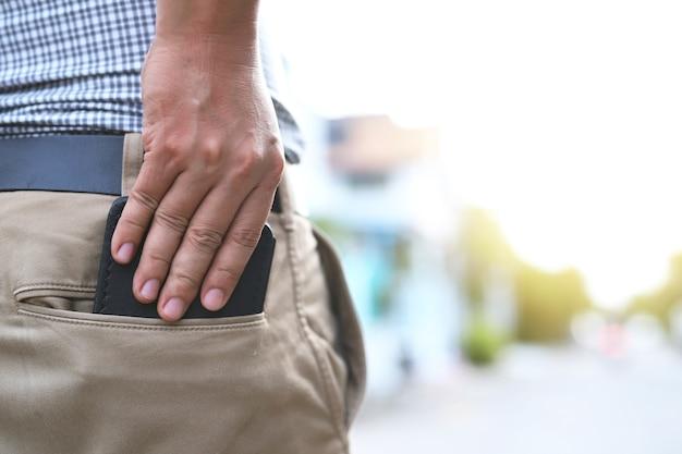 Mężczyzna wyciąga z kieszeni spodni czarną torebkę.